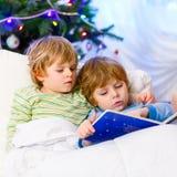 2 маленьких белокурых мальчика отпрыска читая книгу на рождестве Стоковое Изображение