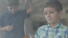 2 маленьких брать близнецов в закоптелой комнате Один мальчик осветил бумагу с лихтером на заднем плане пока другой ребенок акции видеоматериалы