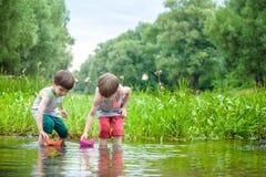 2 маленьких брать играя с бумажными шлюпками рекой на теплый и солнечный летний день Стоковые Фотографии RF