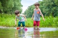 2 маленьких брать играя с бумажными шлюпками рекой на теплый и солнечный летний день Стоковое Фото