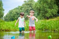 2 маленьких брать играя с бумажными шлюпками рекой на теплый и солнечный летний день Стоковые Изображения