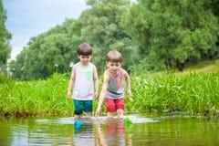 2 маленьких брать играя с бумажными шлюпками рекой на теплый и солнечный летний день Стоковая Фотография RF