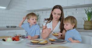 2 маленьких брать с их мамой сделать бургеры смеяться и усмехнуться совместно Семья счастья в кухне видеоматериал