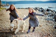 2 маленьких двойных сестры на прогулке с собакой на пляже Стоковая Фотография