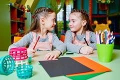 2 маленьких двойных сестры рисуют и жизнерадостно тратят время в ga Стоковое Изображение RF
