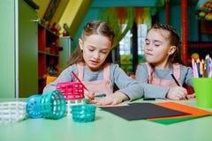 2 маленьких двойных сестры рисуют и жизнерадостно тратят время в ga Стоковое Фото