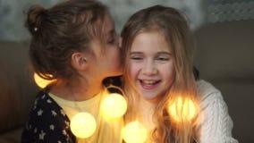 2 маленьких девушки делят секреты Девушка шепча в ухе ее сестры, обоих смеясь весело, вечер рождества, новый видеоматериал