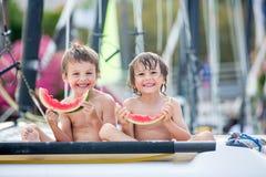 2 маленьких дет, братья мальчика, есть арбуз на beac Стоковые Фотографии RF