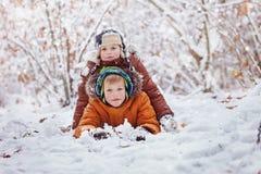 2 маленьких дет, братья мальчика играя и лежа в outd снега Стоковая Фотография