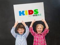 2 маленьких дет держа чистый лист бумаги покрывают над их головами Стоковое Фото
