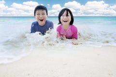 2 маленьких дет играя волны на пляже Стоковые Изображения RF
