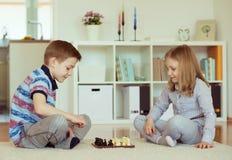 2 маленьких дет играя шахмат дома Стоковые Изображения