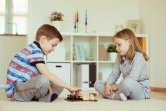 2 маленьких дет играя шахмат дома Стоковая Фотография RF