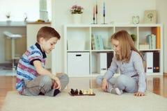 2 маленьких дет играя шахмат дома Стоковые Изображения RF