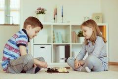 2 маленьких дет играя шахмат дома Стоковое Фото