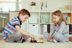 2 маленьких дет играя шахмат дома Стоковая Фотография