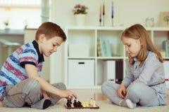 2 маленьких дет играя шахмат дома Стоковые Фото