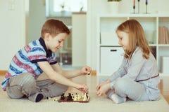 2 маленьких дет играя шахмат дома Стоковые Фотографии RF