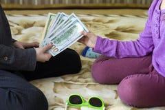 2 маленьких дет мальчик и девушка играя с деньгами долларов Стоковая Фотография RF