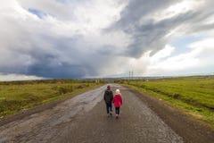 2 маленьких дет мальчик и девушка идя на дорогу Стоковая Фотография