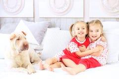 2 маленьких дет обнимающ и смеющся над в пижамах Собака Th Стоковая Фотография