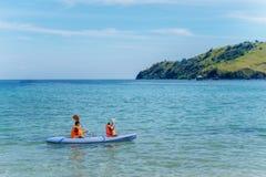 2 маленьких дет canoeing на тропическом пляже Стоковая Фотография RF