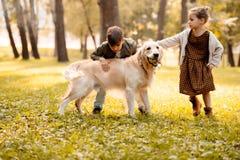 2 маленьких дет petting собака Стоковая Фотография RF
