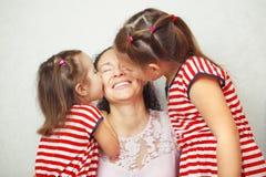 2 маленьких дочери целуют их мать в щеках Стоковое Фото