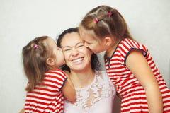 2 маленьких дочери целуют их мать в щеках Стоковые Изображения
