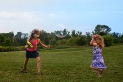 2 маленьких кавказских девушки играя с пузырями и иметь потеху на поле летом стоковые фото