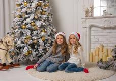 2 маленьких милых девушки в красных крышках рождества сидят около t Стоковое Изображение