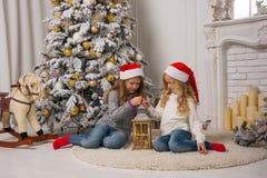 2 маленьких милых девушки в красных крышках рождества сидят около t Стоковая Фотография