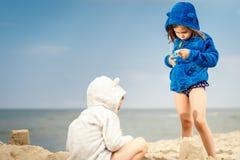 2 маленьких милых девушки играя на песке на пляже Стоковое фото RF