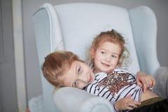 2 маленьких сестры в пижамах сидя в стуле стоковые изображения rf