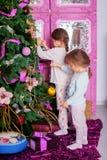 2 маленьких сестры в пижамах украсили рождественскую елку Christma стоковые фотографии rf