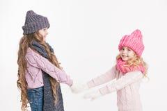 2 маленьких сестры держа руки в одеждах зимы серый пинк Семья Зима Стоковое фото RF