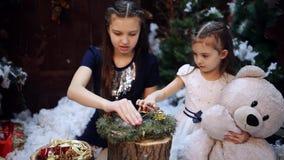 2 маленьких сестры на рождественской елке подготавливают подарок для бабушки Счастливые девушки и семья 2 маленькой девочки на a акции видеоматериалы