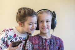 2 маленьких счастливых девушки совместно слушая к музыке 2 маленькой девочки смеясь над пока слушающ к музыке Стоковые Изображения