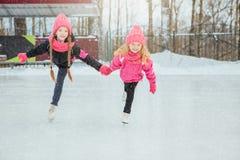 2 маленьких усмехаясь девушки катаясь на коньках на льде в розовой носке и ручной работы шарфах напольно Зима стоковое изображение rf