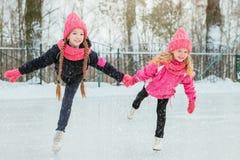 2 маленьких усмехаясь девушки катаясь на коньках на льде в розовой носке и ручной работы шарфах напольно Зима стоковое изображение