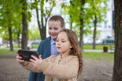 2 маленького ребенка принимая selfie внешнее Концепция потехи приятельства влюбленности Малые взрослые стоковые фотографии rf
