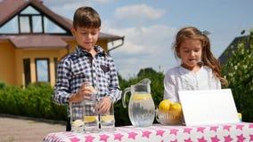 2 маленького ребенка продают лимонад на домодельной стойке лимонада на солнечный день с знаком цены для предпринимателя Стоковое Изображение RF