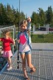 Маленькое кавказское белокурое положение девушки 2 на доке с рыболовной удочкой и шоу уловило рыб стоковое изображение rf