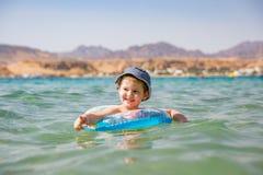 Маленькое милое плавание мальчика в море Счастливая игра мальчика, плавая в море с раздувным кольцом стоковые фотографии rf