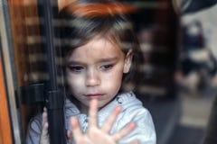 Маленькое плача положение девушки за стеклянными родителями двери и искать ребенок унылый стоковое фото rf