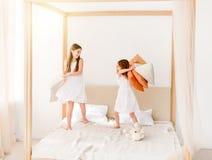 2 маленькой девочки воюя с подушками на кровати Стоковые Фото