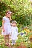 2 маленькой девочки в белых платьях и венке цветка имея потеху сад лета стоковые фотографии rf