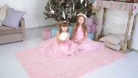 2 маленькой девочки играют совместно и смеются над около рождественской елки видеоматериал