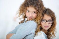 2 маленькой девочки, который стоят спина к спине Стоковые Изображения