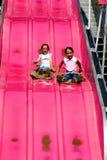 2 маленькой девочки наслаждаясь длинным скольжением стоковые изображения rf